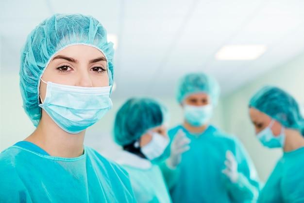 Jonge vrouwelijke chirurg met medisch team in rug vóór de operatie