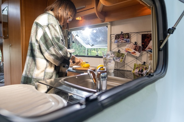 Jonge vrouwelijke citroen snijden op een houten bord