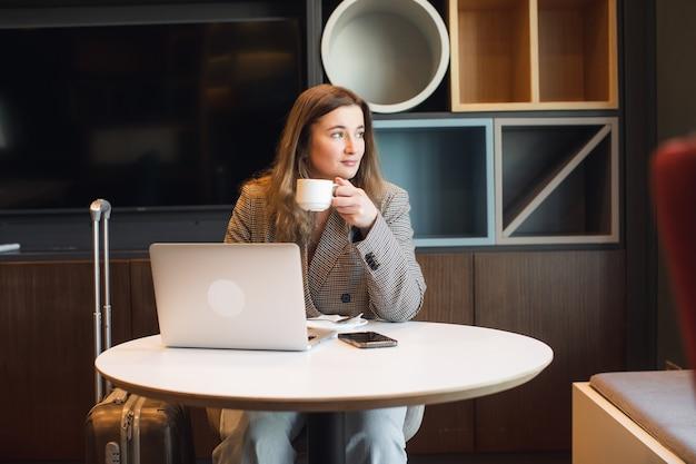 Jonge vrouwelijke copywriter die tekst maakt voor het plaatsen van artikelen op de inhoudswebsite met behulp van een netbook terwijl...