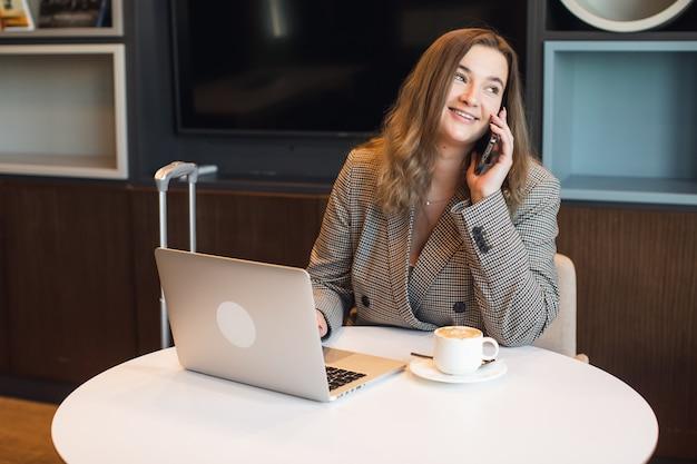 Jonge vrouwelijke copywriter die tekst maakt voor het posten van artikelen op de inhoudswebsite met behulp van een netbook terwijl ze op afstand binnenshuis werkt.