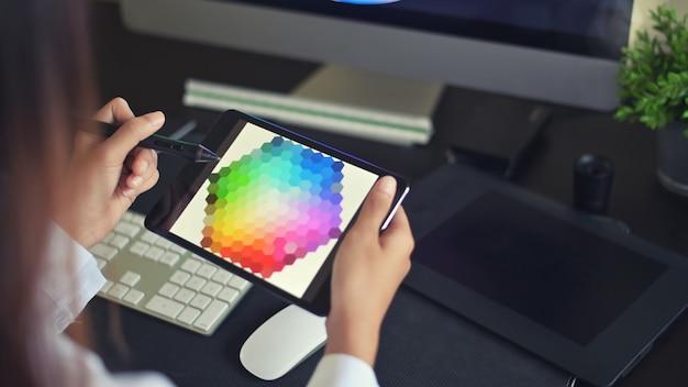 Jonge vrouwelijke creatieve kunstenaar van webdesign met het werken aan kleurselectie op grafische tablet.