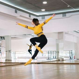 Jonge vrouwelijke danser die in de dansstudio praktizeren