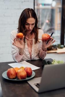 Jonge vrouwelijke diëtist consulteert online en bespreekt de voedingswaarde van voedingsmiddelen.