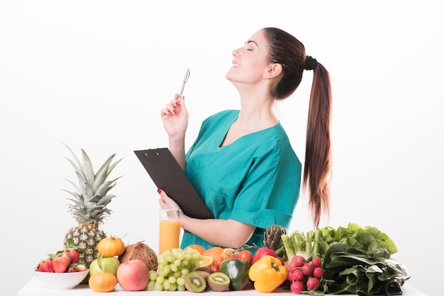 Jonge vrouwelijke diëtist die aan het bureau zit en kleurrijke groenten en fruit laat zien