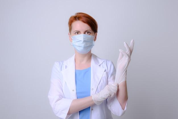 Jonge vrouwelijke dokter in witte jas en beschermend medisch masker trekt latex rubberen handschoen over haar hand