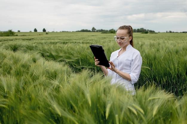 Jonge vrouwelijke ecoloog-wetenschapper in een bril die in een groen veld staat en aan een transparant glasscherm werkt