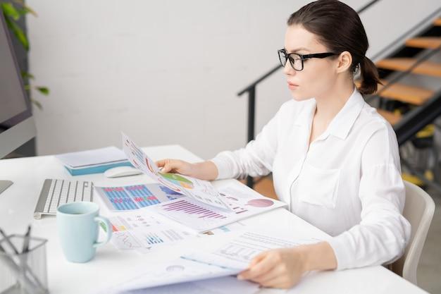 Jonge vrouwelijke econoom of accountant zit door bureau in kantoor en kijkt door financiële documenten
