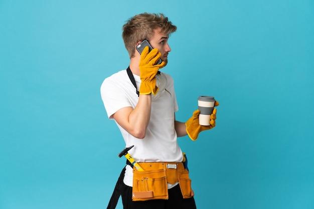 Jonge vrouwelijke elektricien over de geïsoleerde koffie van de muurholding om mee te nemen en een mobiel