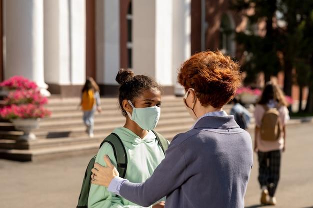 Jonge vrouwelijke en middelbare scholieren met beschermende maskers
