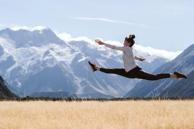 Jonge vrouwelijke enthousiast over yoga en gymnastiek doen een perfecte split jump in de wilde natuur.