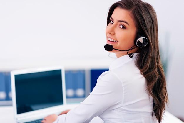 Jonge vrouwelijke exploitant met hoofdtelefoons