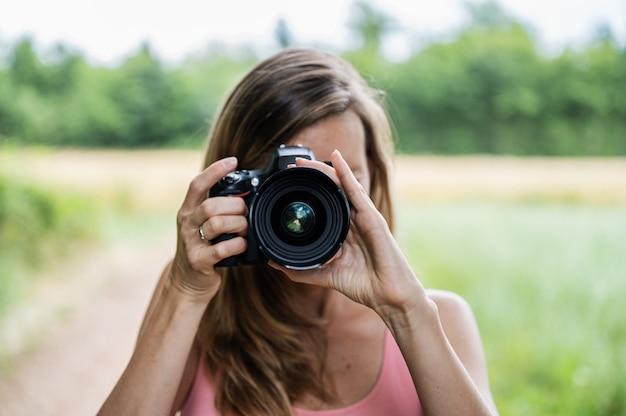 Jonge vrouwelijke fotograaf die een foto direct naar je maakt terwijl je buiten in de natuur staat.