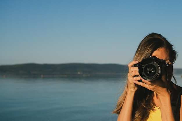 Jonge vrouwelijke fotograaf die foto rechtstreeks op u neemt met zwarte dslr-camera.
