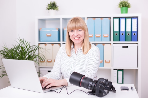 Jonge vrouwelijke fotograaf die op kantoor werkt