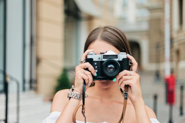 Jonge vrouwelijke fotograaf die retro camera houdt en een foto neemt in stedelijke omgeving