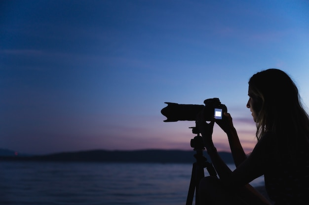 Jonge vrouwelijke fotograaf zet haar camera op een statief in de schemering aan zee.