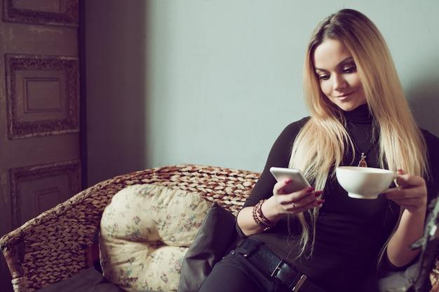 Jonge vrouwelijke freelancer chatten op mobiele telefoon zittend op de bank in vintage café