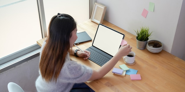 Jonge vrouwelijke freelancer die aan haar project met lege tablet en kleverige nota's werkt