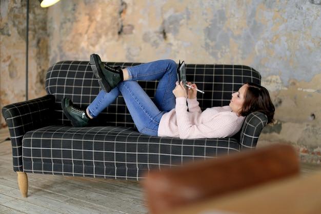 Jonge vrouwelijke freelancer die de tablet van het aanrakingsscherm gebruikt