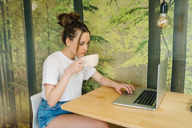 Jonge vrouwelijke freelancer die op laptop werkt ze maakt inhoud met camera en werkt op laptop