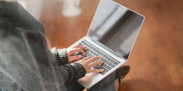 Jonge vrouwelijke freelancer typen op laptopcomputer tijdens het werken aan haar project