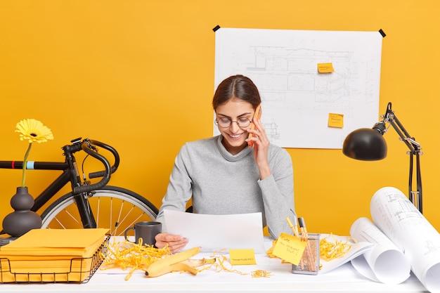 Jonge vrouwelijke freelancer werkt in thuiskantoor heeft telefoongesprek gericht op papieren document bespreekt toekomstig project overlegt met ervaren professionele leider via smartphone poses op desktop