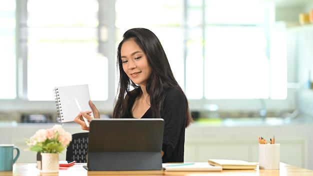 Jonge vrouwelijke gebruikstablet heeft een videogesprek of briefing met diverse collega's.