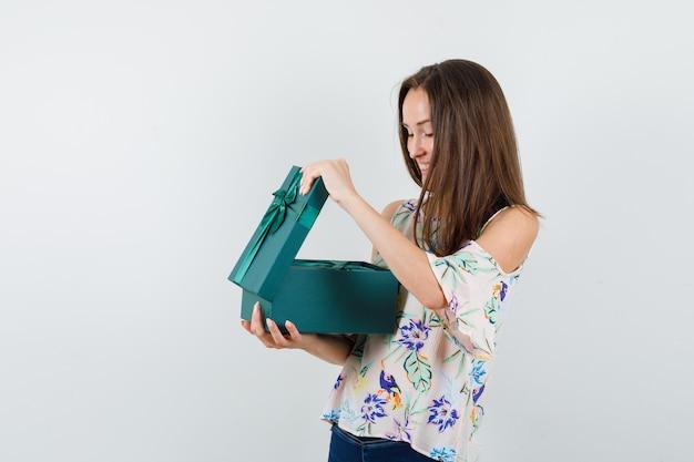 Jonge vrouwelijke geschenkdoos in shirt, spijkerbroek en op zoek gelukkig. vooraanzicht.