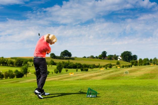 Jonge vrouwelijke golfspeler bij driving range