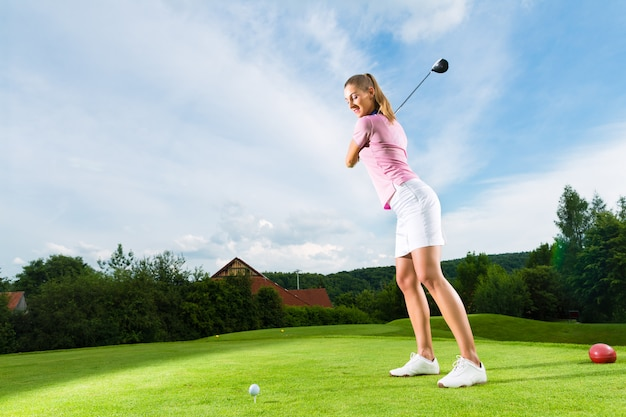 Jonge vrouwelijke golfspeler op cursus die golfschommeling doet