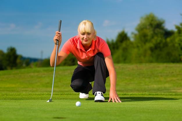 Jonge vrouwelijke golfspeler op cursus die naar zet streeft