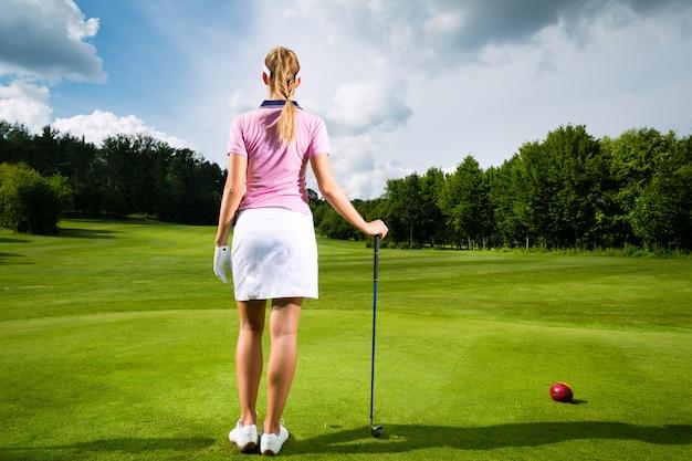 Jonge vrouwelijke golfspeler op cursus
