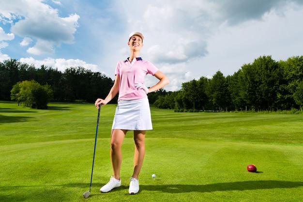Jonge vrouwelijke golfspeler op koers