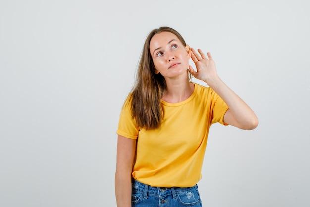 Jonge vrouwelijke hand achter oor om te luisteren in t-shirt, korte broek vooraanzicht.