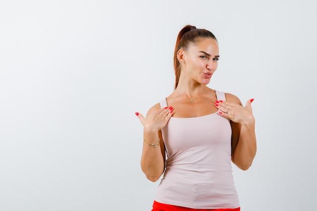 Jonge vrouwelijke hand in hand op de borst in hemd en op zoek trots, vooraanzicht.