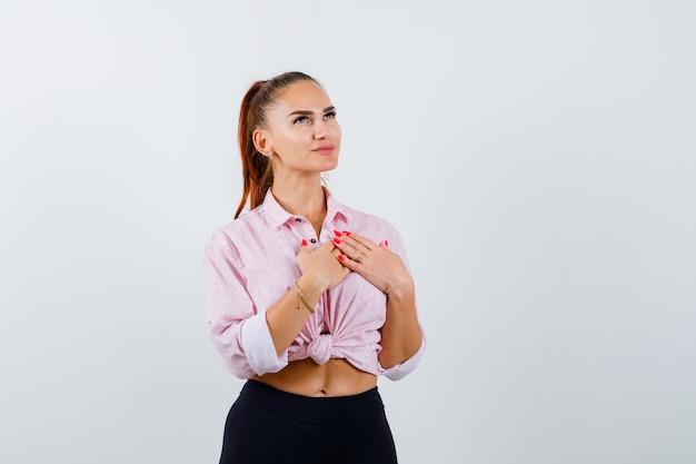 Jonge vrouwelijke hand in hand op de borst om te bidden in casual shirt en hoopvol te kijken. vooraanzicht.