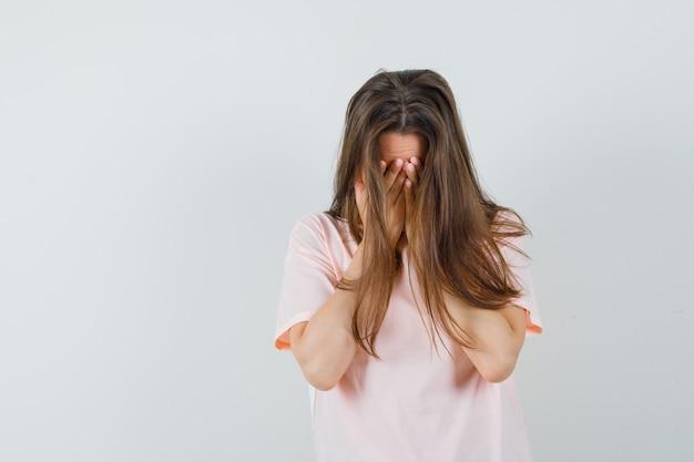 Jonge vrouwelijke hand in hand op gezicht in roze t-shirt en op zoek depressief, vooraanzicht.