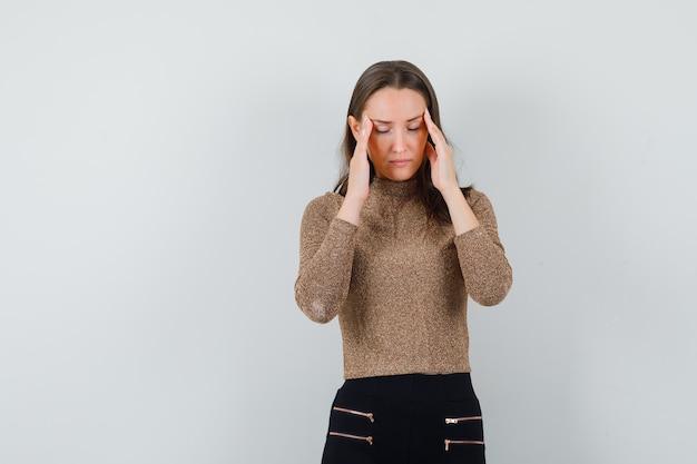 Jonge vrouwelijke hand in hand op haar slapen in blouse, rok en op zoek naar stressvol, vooraanzicht. ruimte voor tekst