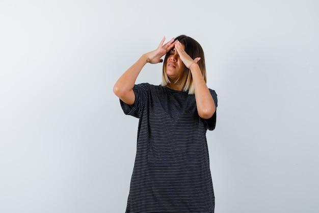 Jonge vrouwelijke hand in hand op het hoofd in polokleding en uitgeput, vooraanzicht kijken.