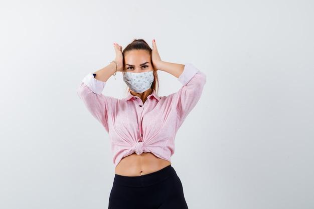 Jonge vrouwelijke hand in hand op het hoofd in shirt, broek, medisch masker en op zoek naar vergeetachtig, vooraanzicht.