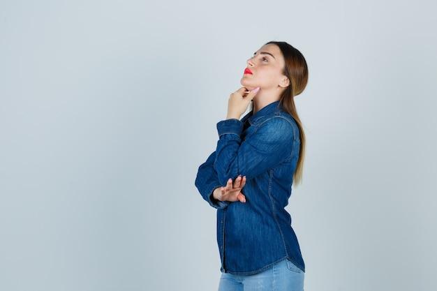 Jonge vrouwelijke hand onder de kin in denimoverhemd en spijkerbroek en op zoek attent