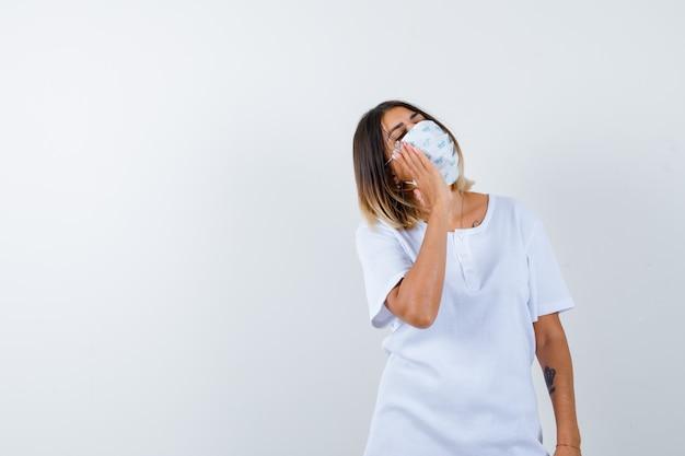 Jonge vrouwelijke hand op de wang terwijl wegkijken in t-shirt, masker en op zoek attent, vooraanzicht.