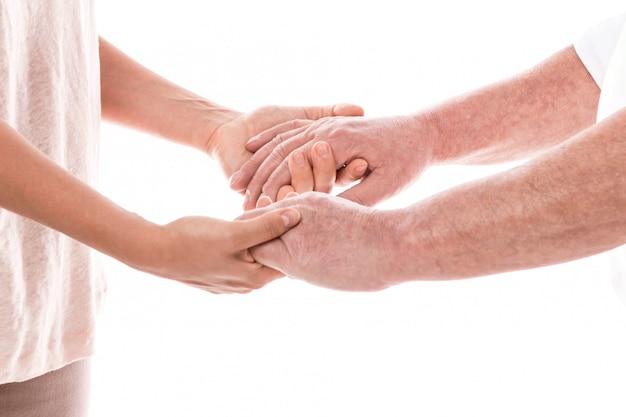 Jonge vrouwelijke handen en oude mannelijke handen
