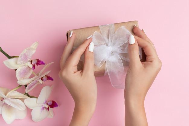 Jonge vrouwelijke handen houden een ambachtelijke geschenkdoos met een witte strik op een roze achtergrond met orchideebloemen