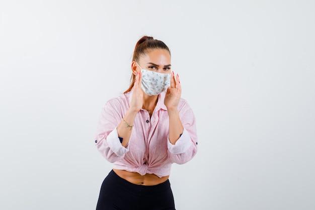 Jonge vrouwelijke handen houden in de buurt van de mond in shirt, broek, masker en nieuwsgierig, vooraanzicht kijken.
