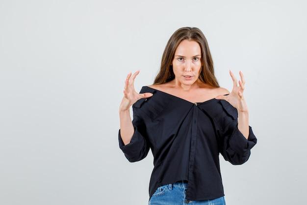 Jonge vrouwelijke handen met woede in zwart shirt, korte broek verhogen en woedend kijken