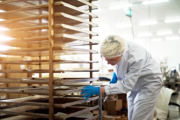 Jonge vrouwelijke hardwerkende bakkerij werknemer in steriele doeken duwen rek met blikjes gevuld met vers gebakken koekjes.