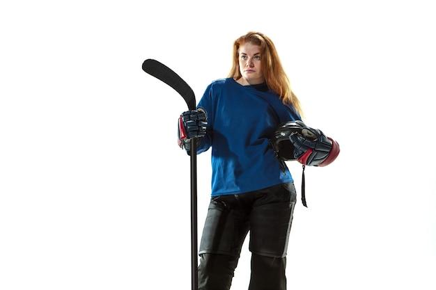 Jonge vrouwelijke hockeyspeler met de stok op ijsbaan en witte achtergrond