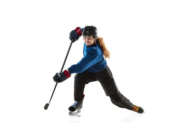 Jonge vrouwelijke hockeyspeler met de stok op ijsbaan en witte muur. sportvrouw die uitrusting en helmtraining draagt. concept van sport, gezonde levensstijl, beweging, actie, menselijke emoties.
