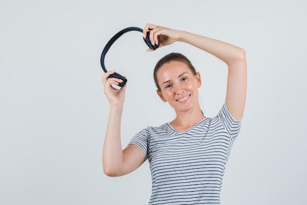 Jonge vrouwelijke hoofdtelefoons in gestreept t-shirt houden en vrolijk kijken. vooraanzicht.